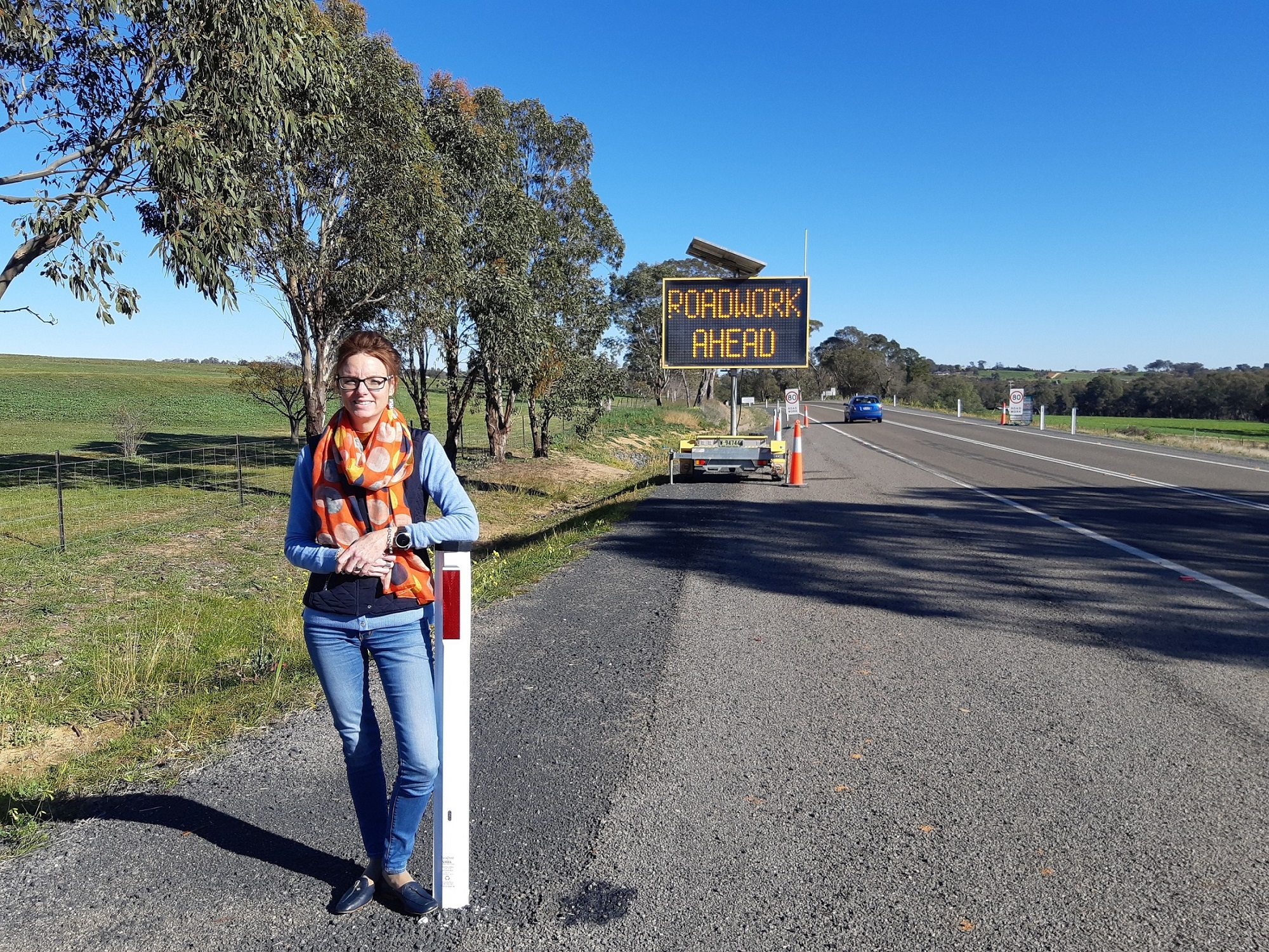 Steph Cooke stands on the side of a road and leans on a guide post. A 'Roadwork Ahead' sign can be seen behind her.